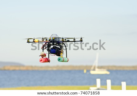 Remote-controlled surveillance helicopter  flying towards yacht carrying camera - stock photo