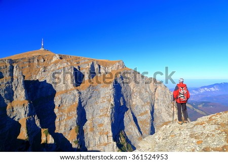 Remote mountaineer standing on the edge and admiring distant rock walls, Bucegi mountains, Romania - stock photo