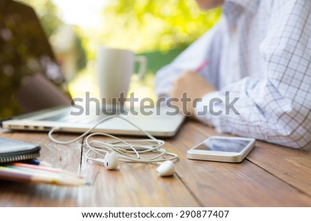 Remote office concept Business style dressed man sitting at natural country style wooden desk with electronic gadgets around working on laptop drinking coffee sunlight and green terrace on background  - stock photo