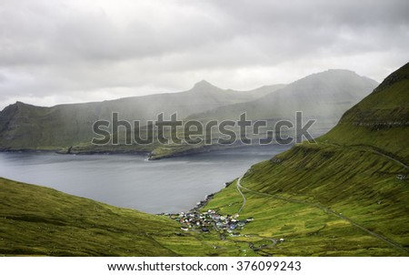 Remote small village surrounded by nature of Faroe Islands. Faroe Islands : typical nordic village overlooking a fjord surrounded by green mountains  - stock photo