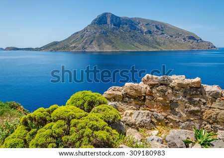 Remote volcanic Island seen from Greek Island Kalymnos with green bushes and clear blue sky, Greece - stock photo