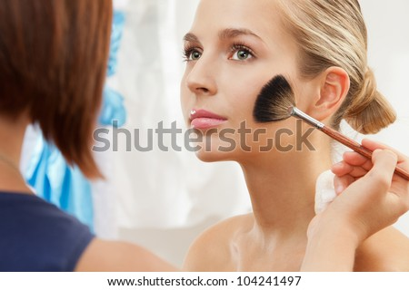 removing excess of powder using fan brush - professional makeup artist working - stock photo