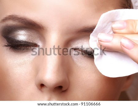 Removing makeup - closeup portrait of a pretty young woman using cotton on closed eyes - stock photo
