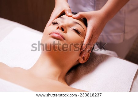 Removing stress. Beautiful young woman lying on back while massage therapist massaging her head  - stock photo
