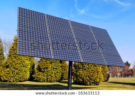 Renewable clean green electric energy generating efficient photovoltaic solar panels array on a mounting pole in an industrial installation application - stock photo