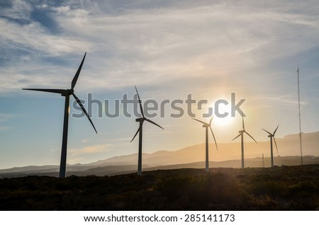 Renewable Energy Concept Windmil Farm at Sunset - stock photo