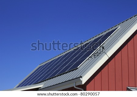 Renewable energy panels collecting the suns energy on an outdoor roof of a public building under a sunny blue sky. - stock photo
