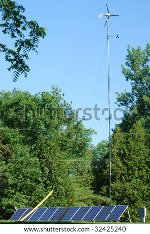 renewable energy- solar panels and windmill with trees - stock photo