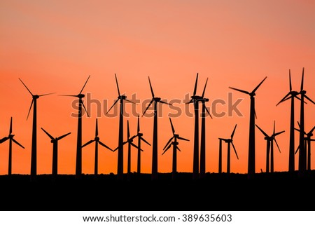 Renewable energy windmills line the mountaintops of Palm Springs at sunset - stock photo