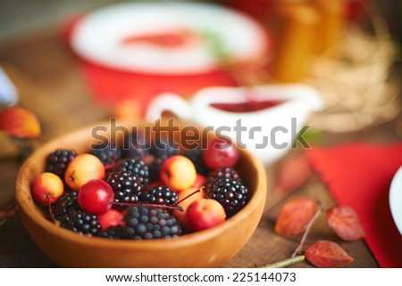Rennets and blackberries on served table - stock photo