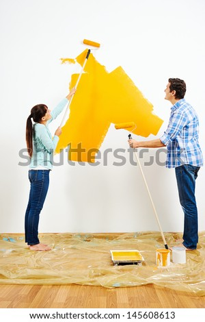 renovation diy paint couple in new home painting wall - stock photo