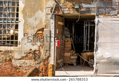 renovation of an old building on a narrow canal, venice - stock photo
