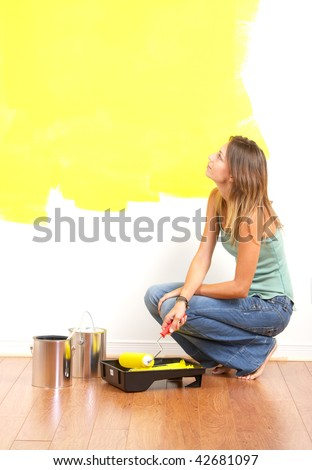 Renovation. Smiling beautiful woman painting interior wall of home. - stock photo