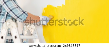 repair and home renovation concept - close up of male hand in gloves painting a wall with yellow paint - stock photo