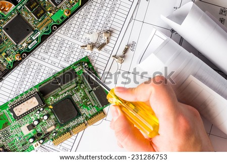 Repair broken computer, the hand holding a screwdriver - stock photo