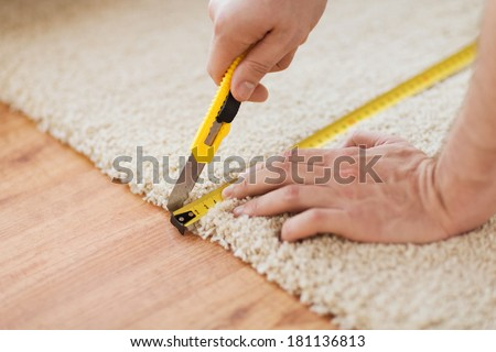 repair, building and home concept - close up of male hands cutting carpet with blade - stock photo