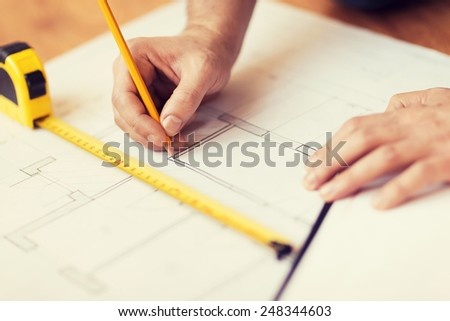 repair, building and home concept - close up of male hands making changes to blueprint - stock photo