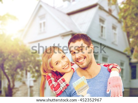 repair, building and home concept - smiling couple covered with paint with paint brush - stock photo