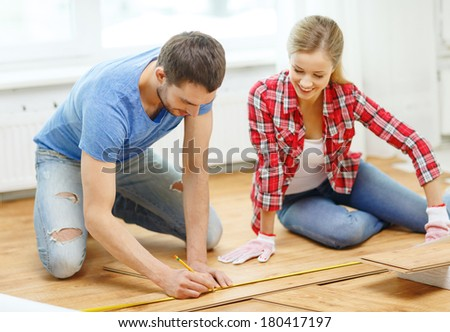 repair, building and home concept - smiling couple measuring wood flooring - stock photo