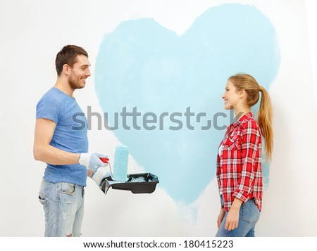 repair, building and home concept - smiling couple painting big heart on wall at home - stock photo