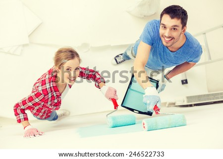 repair, building and home concept - smiling couple painting wall at home - stock photo