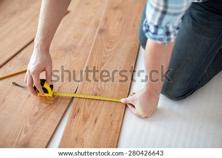 repair, building, floor and people concept - close up of male  hands measuring wooden flooring with ruler and making mark by pencil - stock photo