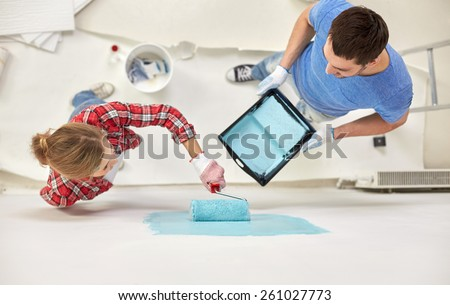 repair, building, people, teamwork and renovation concept - couple with paint and roller painting wall at home - stock photo