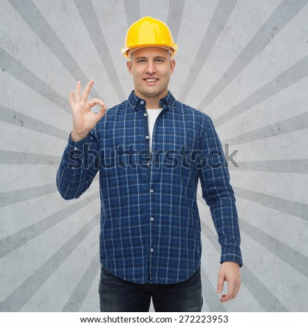 repair, construction, building, people and maintenance concept - smiling male builder or manual worker in helmet showing ok sign over gray burst rays background - stock photo