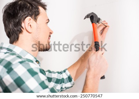 Repair home concept. Young man hammer a nail. - stock photo