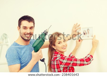 repair, interior design, building, renovation and home concept - smiling couple drilling hole in wall and putting picture up at home - stock photo