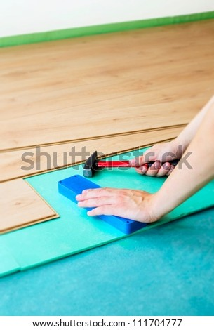Repair of a floor covering. Man laying the floor panels - stock photo