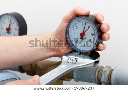 Repair of a pressure gauge with wrench - stock photo