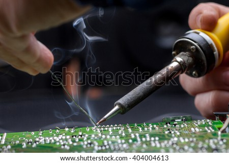 Repair of electronic devices, tin soldering parts - stock photo