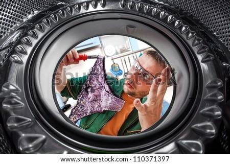 Repair of washing machine. A man found a women's panties - stock photo