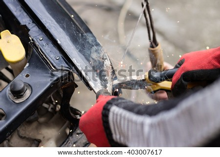 Repair service worker fix damaged car after crash on the road. Working with welding tool to fix metal body. - stock photo