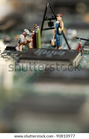 Repairing Electronic Circuitry. A miniature model figurine of a welder at work on a circuit board, macro. - stock photo