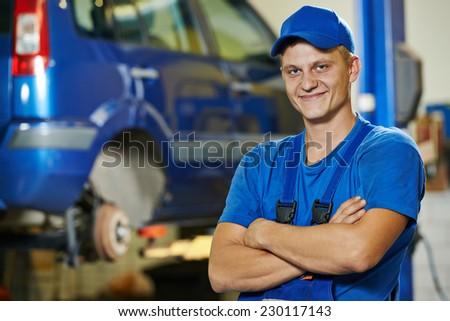 repairman auto mechanic Portrait in car auto repair or maintenance shop service station - stock photo