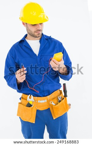 Repairman examining multimeter while standing against white background - stock photo