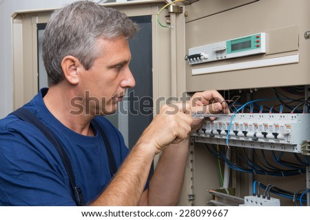 Repairman Fixing An Electric Switchboard Indoor - stock photo