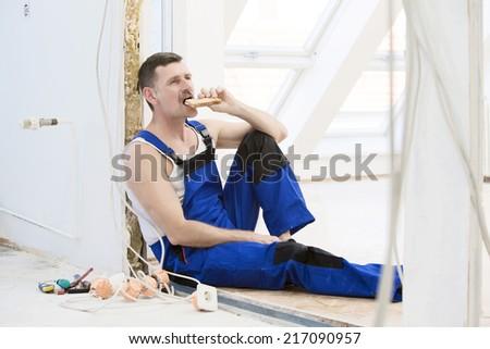 repairman having a break and eating a sandwich - stock photo