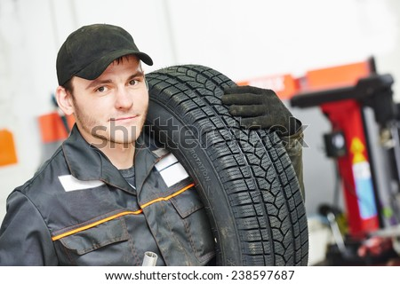 repairman mechanic portrait in car auto repair or maintenance shop service station with automobile wheel tire - stock photo