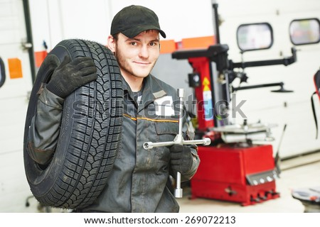 repairman mechanic portrait with tyre in car auto repair or maintenance shop service station with automobile wheel tire - stock photo