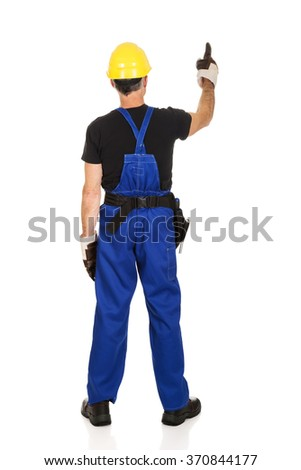 Repairman wearing hard hat pointing up - stock photo