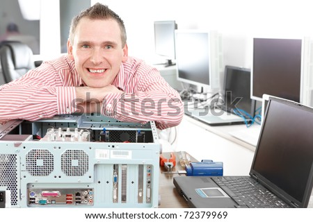 Repairman with computer, an owner of small business. Monitors and other laptops in the background waiting for service. - stock photo