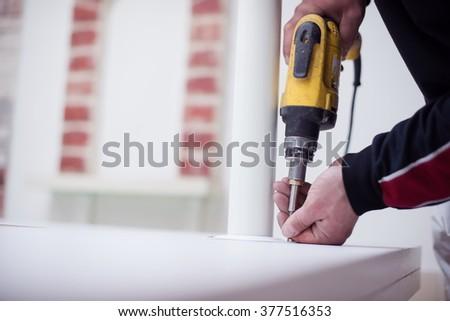 repairman working with drilling machine and assambling  furniture - stock photo