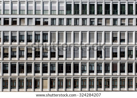Repetition of windows of a white office building, some with shutters closed some with shutters open. Direct sunlight.  - stock photo