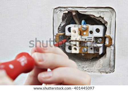 Replacing damaged light switch, disassembly of the old appliance close-up.  - stock photo
