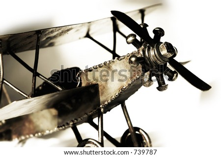 Replica of vintage biplane, close up with shadow on white - transportation and travel. - stock photo
