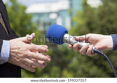 Reporter interviewing a businessman  - stock photo