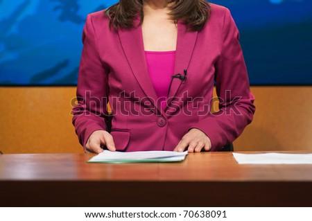 Reporter presenting news in TV studio - stock photo